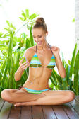 Woman in bikini enjoying her music — Stock Photo