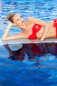 Pretty blonde reclining beside a swimming pool — Stock Photo