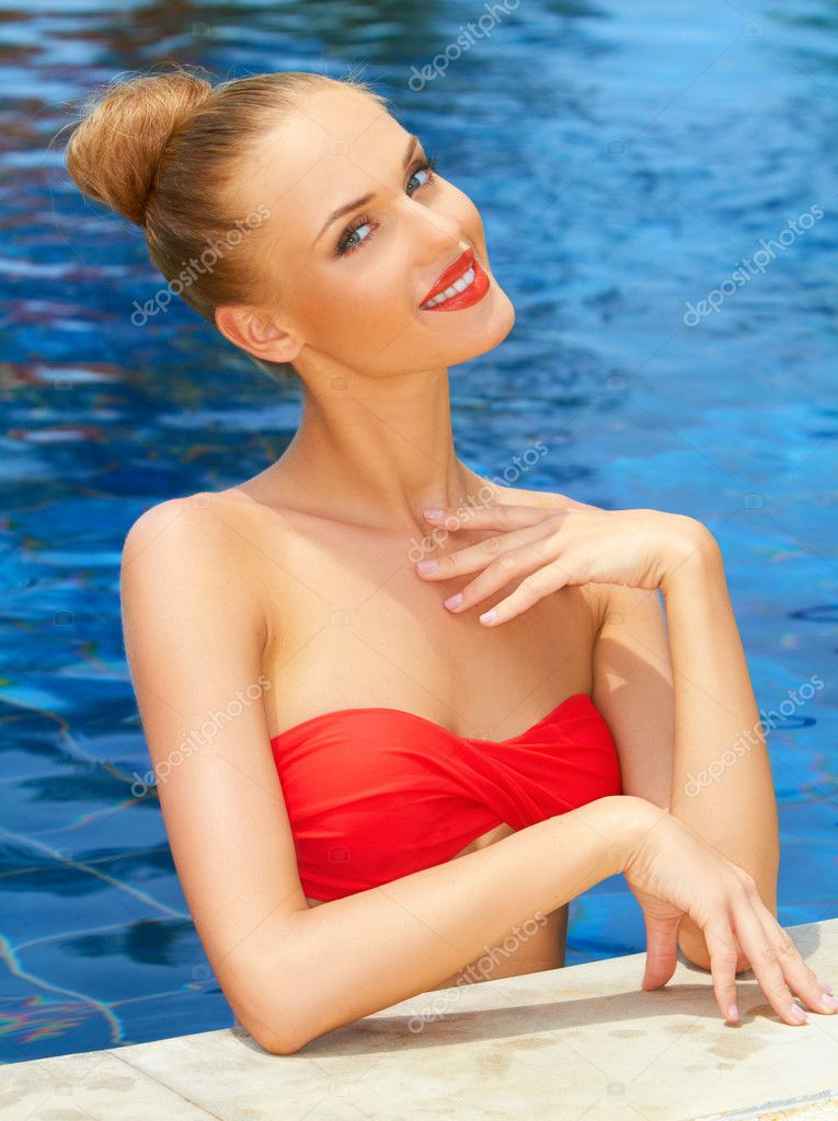 Glamorous blonde woman posing at the edge of the pool with her head tilted to one side — Stock Photo #10862653