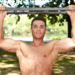 Good looking male doing exercises in park - Stock Photo