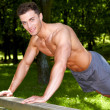 Handsome man in forrest doing exercises — Stock Photo #10904484