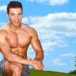 Sporty muscular man at field — Stock fotografie