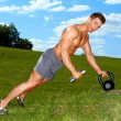 Sporty man practicing with weights — Stockfoto