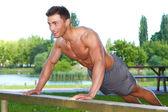 Fitness man in park making push ups — Stock Photo