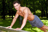 Handsome man in forrest doing exercises — Stock Photo