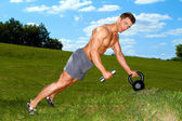 Sporty man practicing with weights — Stock Photo