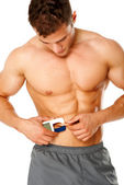 Muscular man measures level of fat on his body — Stock Photo