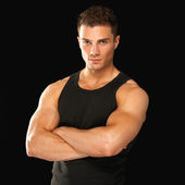 Happy fit male posing over black background — Stock Photo