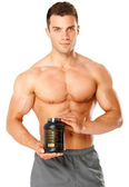 Muscular man holding container of training supplements — Stock Photo
