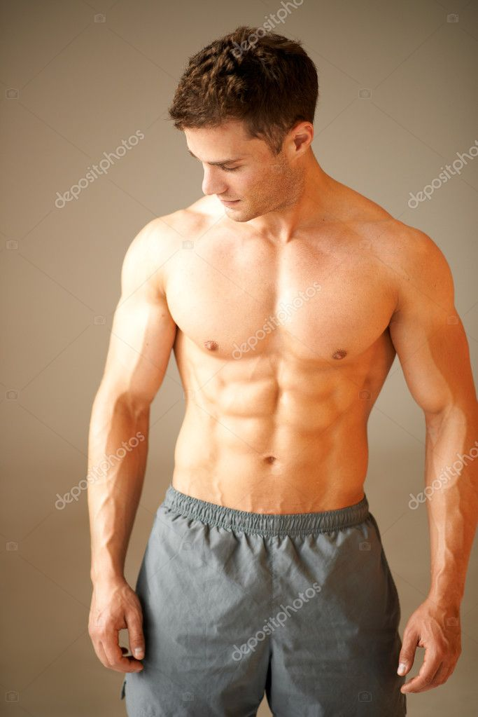 Portrait of muscular sporty man standing on brown background — Stock Photo #11134163
