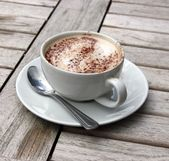 Cup of Cappuccino on wooden slat table — Stock Photo