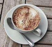 Tasse cappuccino auf hölzernen stab-tabelle — Stockfoto