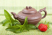 Ceramic tea, mint and strawberries on a green background — Stock Photo