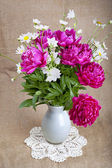 Bouquet of peonies and daisies in a white vase on a lace napkin — Stock Photo