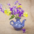 Bouquet of flowers in a ceramic teapot in the background of the - Stock Photo