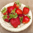 Strawberries in a wicker basket on the background of the canvas - Stock Photo