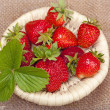 Strawberries with leaves in a wicker basket on the background of - Stock Photo