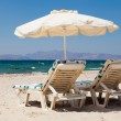 Deckchairs under parasol on sunny beach — Stock Photo