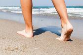 Kvinnan promenader på stranden — Stockfoto