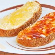 Two pieces of bread with butter and jam — Stockfoto