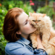 Stock Photo: Young woman with Persian cat playing