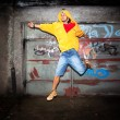 Young man jumping on grunge wall — Stock Photo #11642389