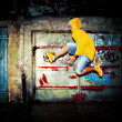 Young man jumping on grunge wall — Stock Photo