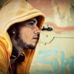 Young man portrait on graffiti grunge wall — Stock Photo