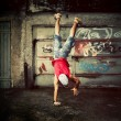 Young man jumping on grunge wall — Stock Photo #11642697