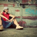 Young man sitting. Grunge graffiti wall — Stock Photo