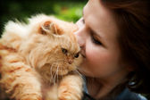 Young woman with Persian cat playing — Stock Photo