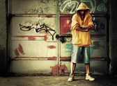 Young man in hooded sweatshirt on grunge wall — Stock Photo