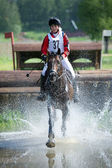 Woman eventer on horse is run in Water jump — Stock Photo