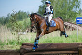 Woman eventer on horse is Drop fence in Water jump — Stock Photo