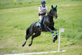 Rider eventer on horse negotiating cross-country fence open ditch — Stock Photo