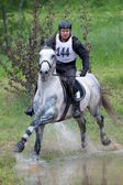Eventer on horse is overcomes the Water jump — Stock Photo