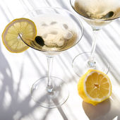 Top view of martini alcohol cocktail with yellow lemon on white with shadows — Stock Photo