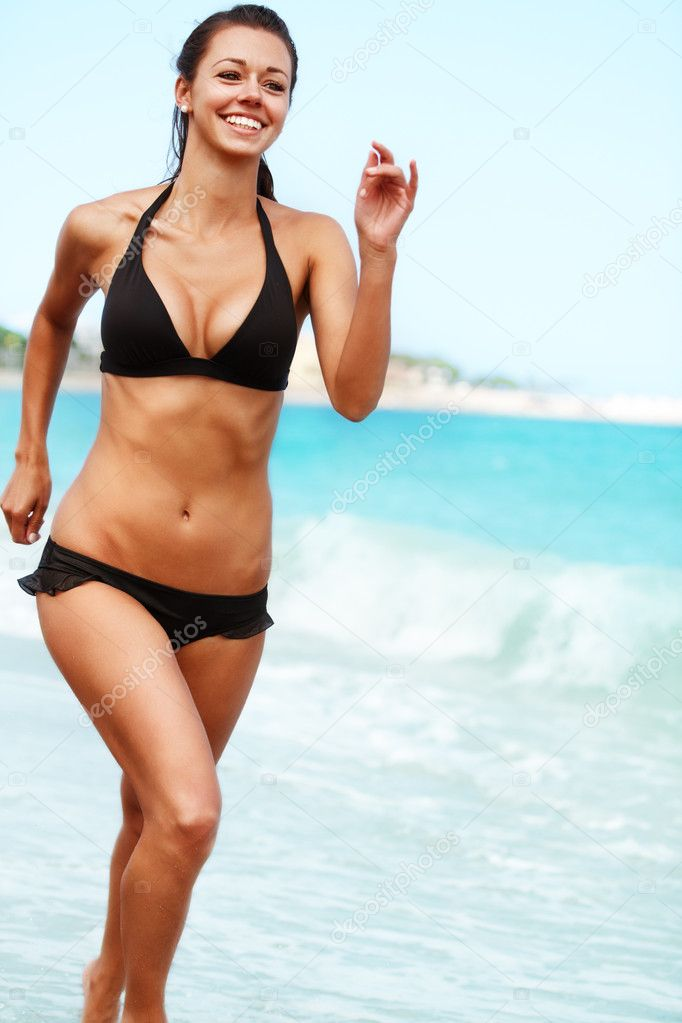 Young attractive woman jogging on the beach  Stock Photo #11596571