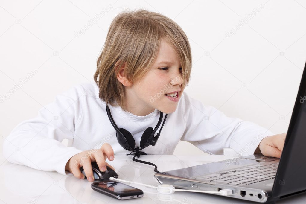 A happy young boy looks something on the Internet — Stock Photo #10828344