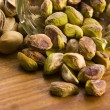 Roasted pistachios on natural wooden table — Stock Photo