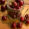Stock Photo: Cherry in glass jar isolated on wooden background