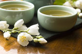 Green tea with jasmine in cup and teapot on wooden table — Stock Photo