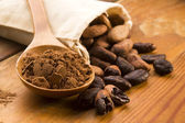 Cocoa (cacao) beans on natural wooden table — Fotografia Stock