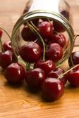 Cherry in glass jar isolated on the wooden background — Stock Photo