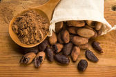 Cocoa (cacao) beans on natural wooden table — Stock Photo