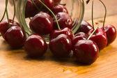 Cherry v sklenice izolovaných na dřevěné pozadí — Stock fotografie