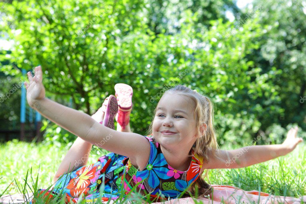 可爱的小女孩玩在绿色草地上