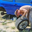 Senior man changing a wheel of his car — Stock Photo #11949202