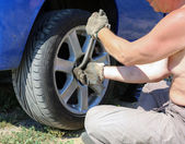 Senior man changing a wheel of his car — Stockfoto