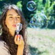 Romantic young girl inflating colorful soap bubbles in park — Stock Photo